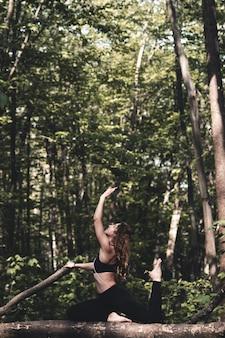 Frau macht sport und hört musik im wald und macht übungen joggen