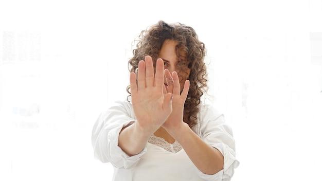 Frau macht stop-geste mit ihrer hand auf einem weißen hintergrund. schöne frau mit lockigem haar in weißen dessous zu hause