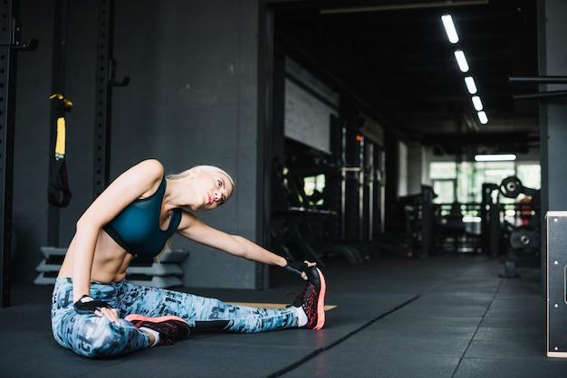 Frau macht stretching im fitness-studio