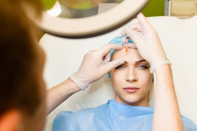 Frau macht verjüngende gesichtsspritzen verfahren zum straffen und glätten von falten im stirnbereich