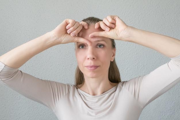Frau macht verjüngende übungen für das gesicht