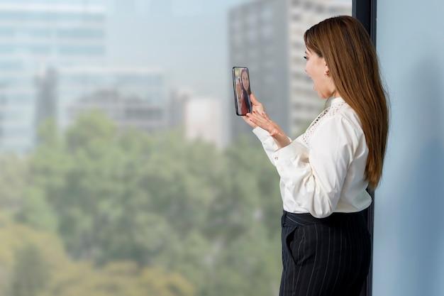 Frau macht videoanrufe mit ihrem handy konzept der arbeit zu hause
