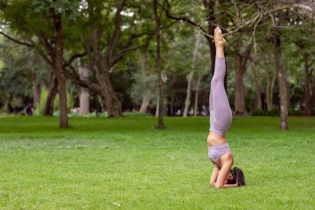 Frau macht yoga-asanas im park auf dem gras mit bäumen im hintergrund