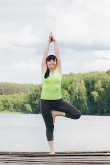 Frau macht yoga auf der brücke im sommer