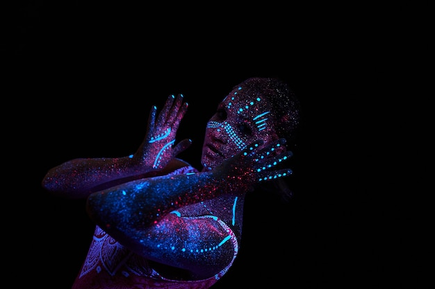 Frau macht yoga, handbewegung, aufwärmen des körpers. kunstmädchenkosmos im ultravioletten licht. der gesamte körper ist mit farbigen tröpfchen bedeckt. astral-yoga. rauschen, unscharf
