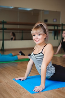 Frau macht yoga-übungen im fitnessstudio, sport fitness girl training stretching studio