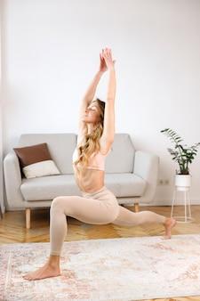Frau macht yoga zu hause im wohnzimmer