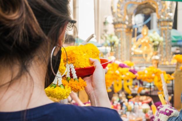 Frau macht zeremonielle opfergaben aus blumengirlanden am erawan-schrein in bangkok, thailand