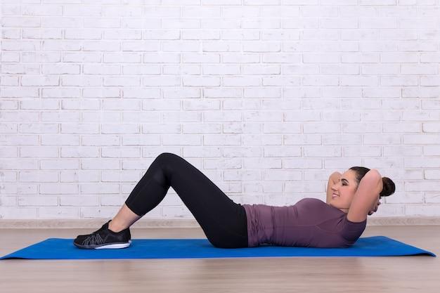 Frau macht zu hause übungen für bauchmuskeln