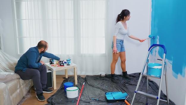 Frau malerei wand mit walzenbürste während der heimdekoration. paar in heimtextilien und renovierung in gemütlicher wohnung, reparatur und verjüngungskur