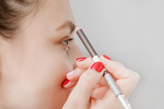 Frau malt augenbrauen vor spiegel. schönes mädchen malen augenbrauen braun. mädchen, das make-up vor einem spiegel tut. das mädchen kümmerte sich um ihr gesicht.