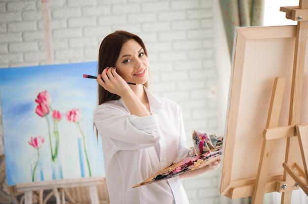 Frau malt bild auf leinwand mit ölfarben in ihrem studio