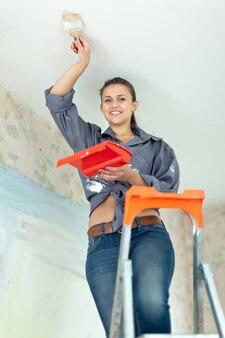 Frau malt decke mit pinsel