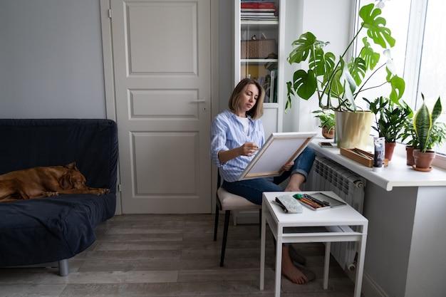 Frau malt ein bild auf leinwand, am fenster zu hause während der sperrung sitzen. hund schläft auf der couch