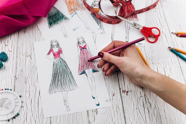 Frau malt ein bild eines kleides auf dem tisch mit nähenden zusätzen