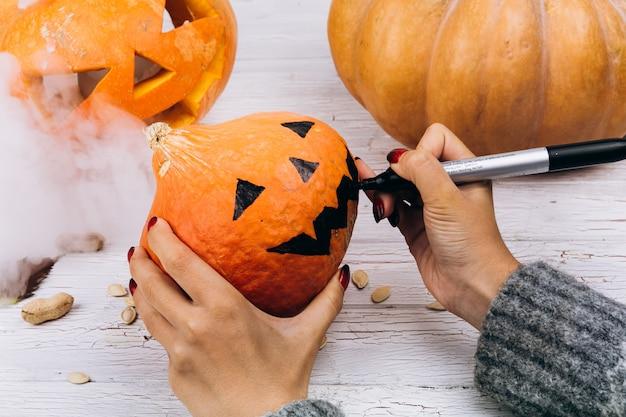Frau malt ein gesicht auf einem kleinen orange kürbis für halloween