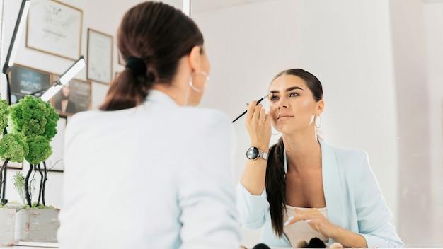 Frau malt ihre augenbrauen und schaut in einen spiegel in einem schönheitssalon