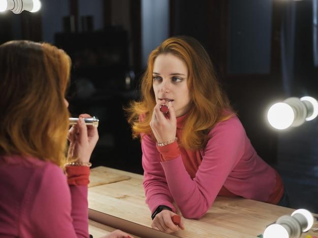 Frau malt ihre lippen mit rotem lippenstift in der nähe des spiegels Premium Fotos