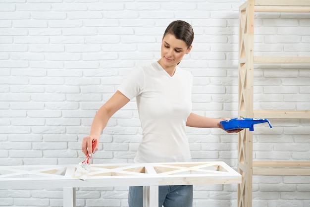 Frau malt mit weißer farbe altem holzgestell