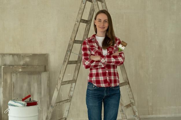 Frau malt wände zu hause hält pinselreparatur und hausrenovierungskonzept