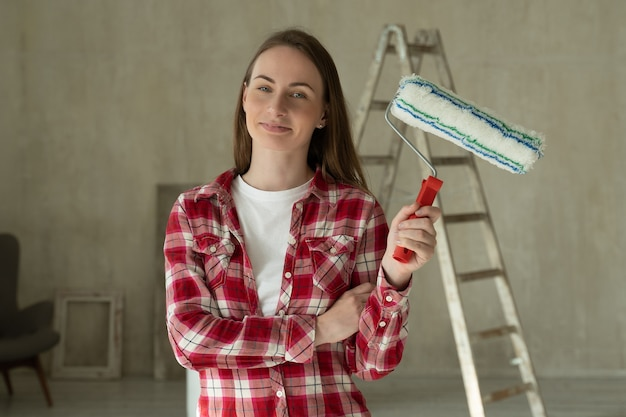 Frau malt wände zu hause hält walzenreparatur und hausrenovierungskonzept