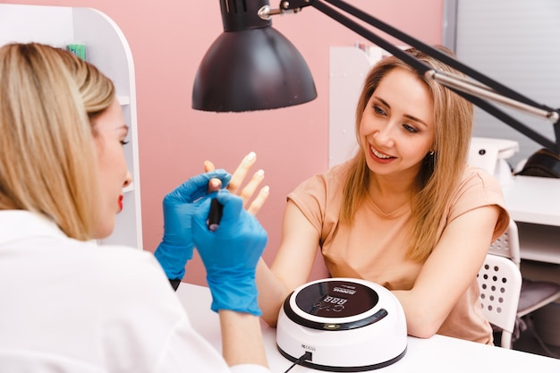 Frau maniküristin bedeckt die nägel mit nagellack für den kunden im schönheitssalon