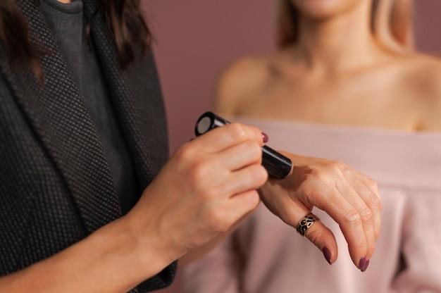 Frau maskenbildner testen schattierungen von bronzer swatch für gesichtsskulptur auf ihrer hand