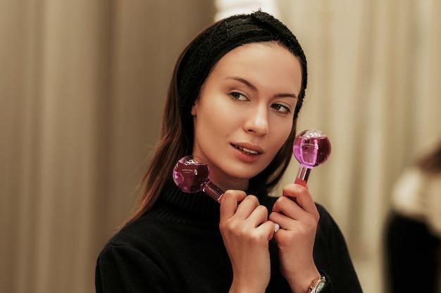 Frau massiert ihr gesicht mit facial ice globes.