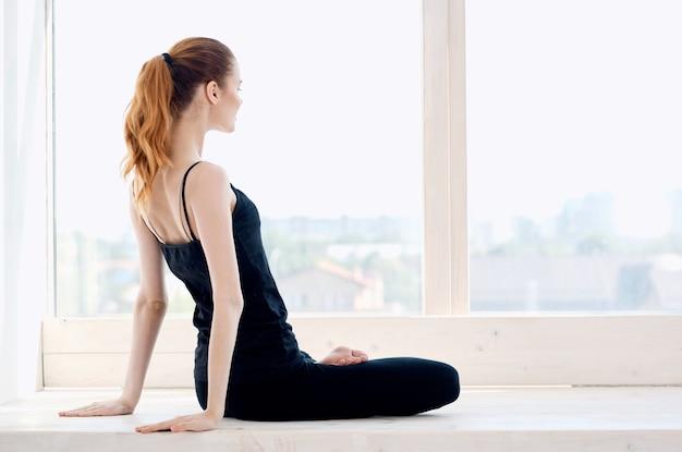 Frau meditiert in der nähe einer ruhigen übung am fenster