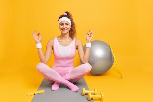 Frau meditiert indoor-praktiken yoga auf fitnessmatte sitzt gekreuzte beine hat regelmäßiges training zu hause, umgeben von sportgeräten isoliert auf gelb