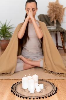 Frau meditiert mit tablett mit kerzen