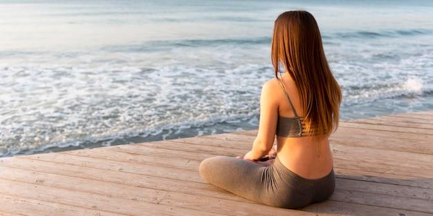 Frau meditiert neben dem meer