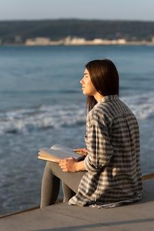 Frau meditiert und liest am strand