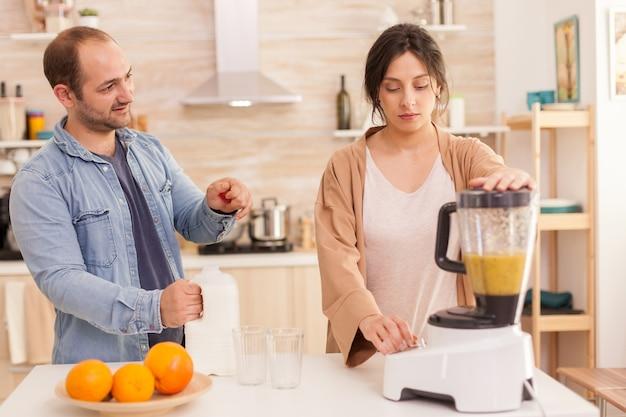Frau mischt früchte in smoothie maker, während ehemann milchflasche öffnet. gesunder, unbeschwerter und fröhlicher lebensstil, ernährung und frühstückszubereitung am gemütlichen sonnigen morgen