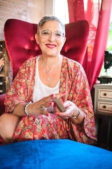 Frau mischt karten, bevor sie die zukunft mit dem tarot-tisch erzählt
