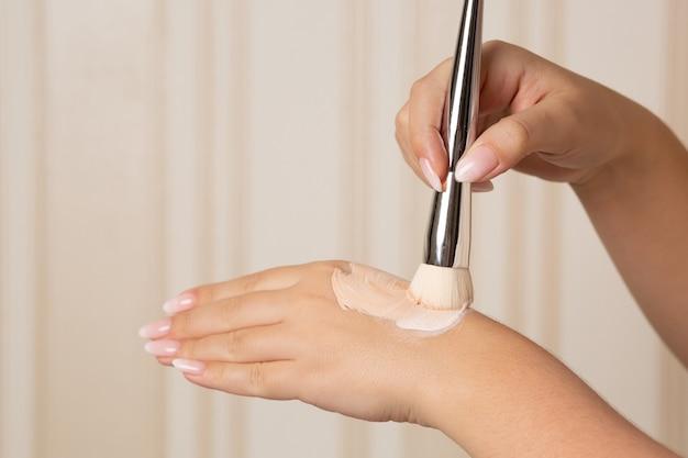 Frau mischt leichte und mittlere foundations auf ihrer hand mit einem pinsel, um einen geeigneten farbton zu finden. platz für text