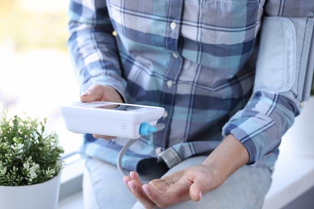 Frau misst den blutdruck mit automatischem tonometer, während sie auf der fensterbank sitzt