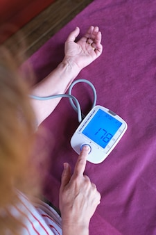 Frau misst den blutdruck mit einem blutdruckmessgerät