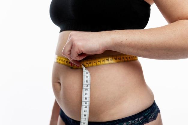 Frau misst fetten bauch. fettleibigkeit und übergewicht.