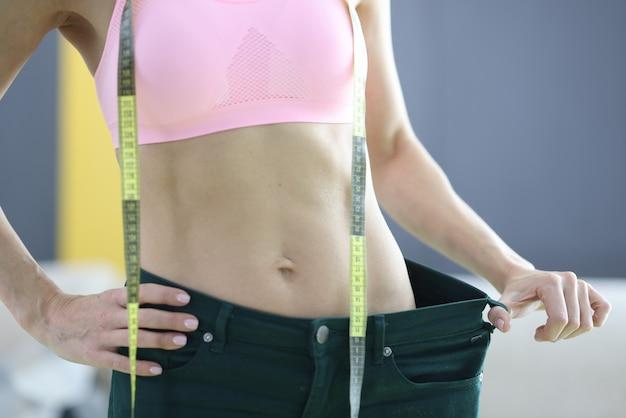 Frau misst ihre alten jeans und zeichnet das ergebnis des abnehmens auf. training und lebensstil für das gesundheitskonzept