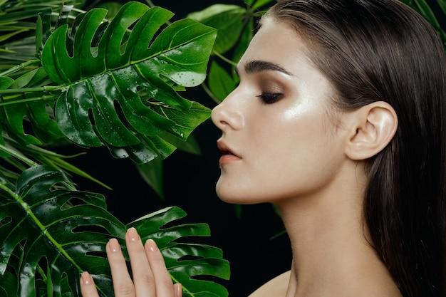 Frau mit abend-make-up auf ihrem gesicht in der nähe von grünen palmenblättern in der natur