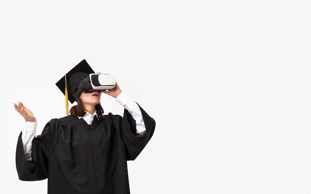 Frau mit abschlussgewand und mütze, die virtual-reality-headset trägt