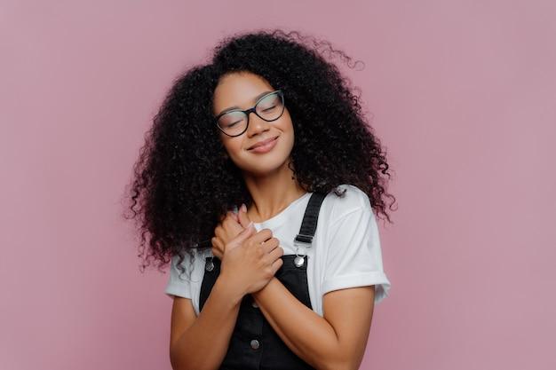 Frau mit afro-frisur, hält die hände auf die brust gedrückt, neigt den kopf