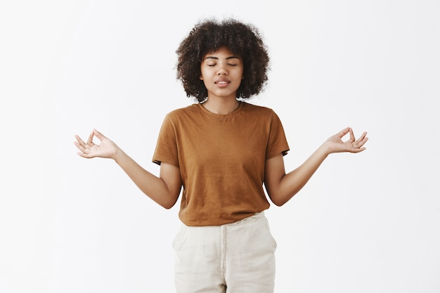 Frau mit afro-frisur und dunkler haut, die die augen schließt und sorglos lächelt und die hände in der zen-geste beiseite legt, um zu meditieren und stress abzubauen
