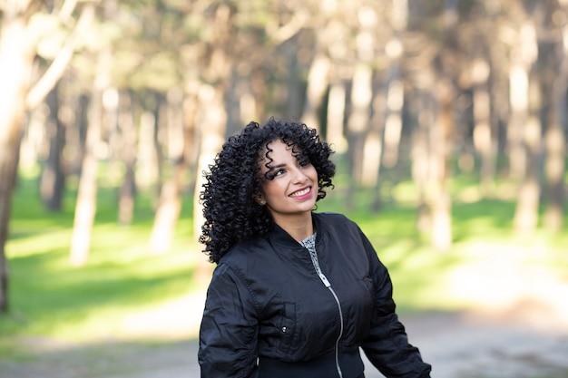 Frau mit afro-haaren, im wald, der spaß glücklich hat