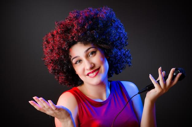 Frau mit afrofrisur singend im karaoke