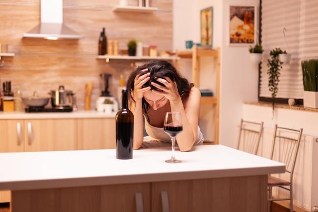 Frau mit alkoholischem getränk trinkt alleine eine flasche wein, die ihren kater bekommt