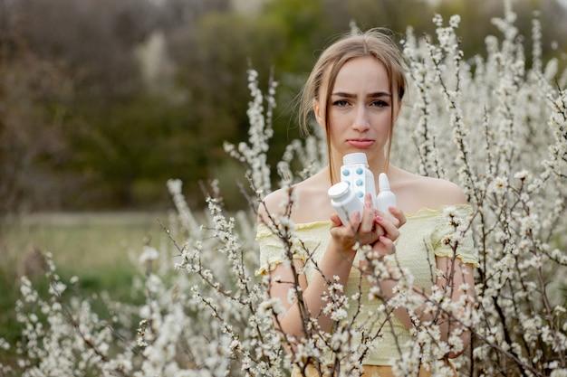 Frau mit allergiemedizin im blütenfeld