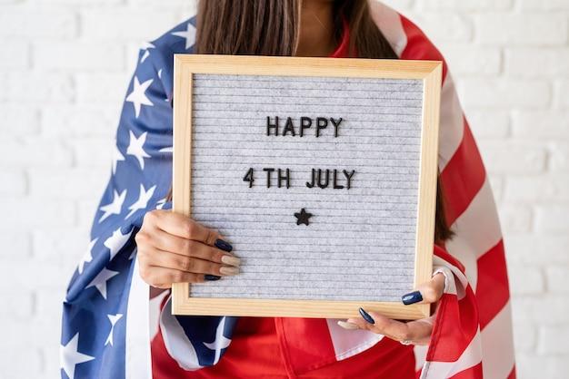 Frau mit amerikanischer flagge, die briefbrett mit worten glücklich 4. juli hält