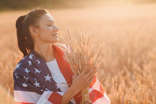 Frau mit amerikanischer flagge und mit einer garbe ohren im weizenfeld bei sonnenuntergang th des patriotischen feiertags des unabhängigkeitstages im juli